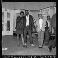 African American youths pose by damaged storefronts in Watts, Los Angeles (Calif.)