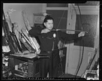 Police officer poses with weapons submitted to the Los Angeles Police Department, Los Angeles, 1942