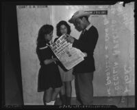 Teenagers read a newspaper story on Japanese submarine casualties