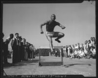 Jesse Owens jumps over a hurdle, Los Angeles, 1930s