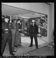 Police officers guard a looted store in Watts, Los Angeles (Calif.)