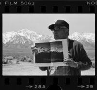 Japanese American man displays book of Ansel Adams' Manzanar photographs