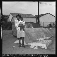 Woman and baby on sidewalk in Watts, Los Angeles (Calif.)