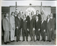 Tom Bradley and others gathered in front of the City of Los Angeles Seal, Los Angeles, 1960s