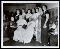 Charlotta Bass at an event with nine other women wearing full-length dresses, 1940s