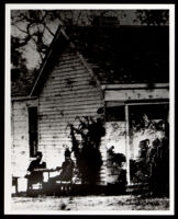 Two men seated at a table beside the Owens family house, Los Angeles, 1884