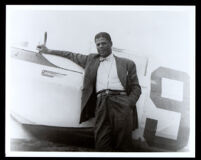 Hubert Julian with his Bellanca airplane, circa 1938-1939