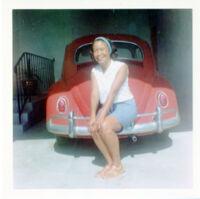 """Sylvia Dorothy """"Dottie"""" Quinn posing with car"""