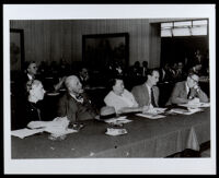 Charlotta Bass is shown seated at a long table probably at a courtroom hearing, 1940s-1950s