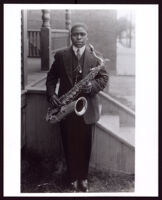 Paul Howard holding his saxophone at the front steps of a house, 1920s