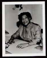 Bessie Bruington Burke seated at a desk, 1955-1968