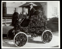 Robert Gaylord seated in a decorated automobile in the Tournament of Roses Parade, Pasadena, 1901