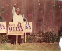 Alfred Thomas Quinn posing with an Elect Al Quinn sign