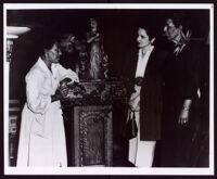 """Beulah Woodard standing beside her work """"Biddy Mason"""" facing two unidentified women, circa 1949"""