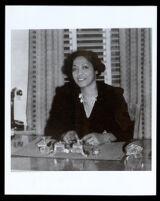 Bessie Bruington Burke seated at a desk, 1930-1945