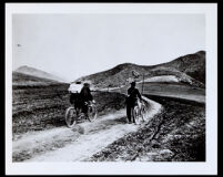 Two bicyclists on an unpaved road at the Cahuenga Pass (?), Los Angeles, 1870-1920