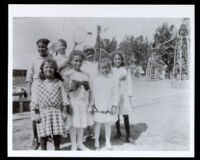 Seven girls in a group photo beside a tennis court, 1910-1930
