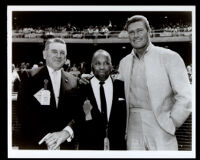 Chuck Connors with Emmett Ashford and another man in a baseball stadium, 1960s