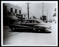 Charlotta Bass in the back seat of a car in front of Hooper Market, 1950-1952