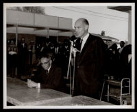 Loren Miller seated beside a man at the opening of the English Square office building, Los Angeles, 1964