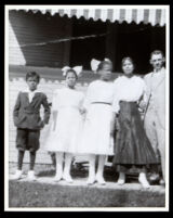 African American family in front of a house with an awning, 1910-1920