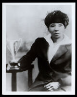 Relative of Bessie Coleman seated beside a trophy cup, 1920s