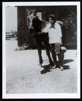 Emily Brown Childress Portwig with a horse outside her desert cabin, Victorville, 1920s-1930s