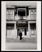 A. J. Roberts in front of the A. J. Roberts, Sons and Company mortuary building on Central Avenue, Los Angeles, 1922 or later