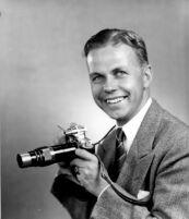 Thelner Hoover - Portrait holding camera, c.1935
