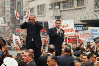 President Johnson covers his ears during a campaign parade in California