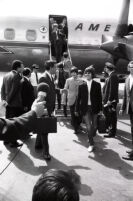 The Beatles are greeted by the press while exiting airplane in Washington D.C. during 1966 American tour