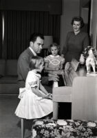 Vice President Richard Nixon playing the piano for Julie, Tricia, and Pat Nixon