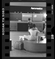 Latino couple comforting each other at LAX after learning of Aeromexico plane crash, 1986