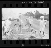 Hazardous materials squad being decontaminated after molten sulfur spill on the 405 Freeway, Calif., 1986