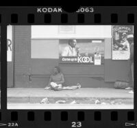 Man sitting on skid row sidewalk below cigarette ads in Los Angeles, Calif., 1986