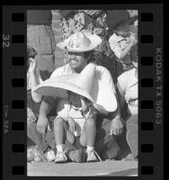 Raymundo Barillas with daughter Sandy wearing sombreros, watching East L.A. Christmas parade, Calif., 1986