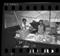 Volunteers making sandwiches for occupants of Tent City II, in Los Angeles, Calif., 1986