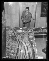 Engineer Heinz Heckeroth points out features on model of Southern California freeways, 1958