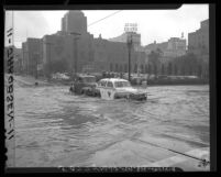 Tow truck pushes stalled taxi across water-filled intersection at 5th and Flower Streets in Los Angeles, Calif., 1948