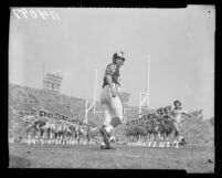 Los Angeles Rams' Jon Arnett running through line of Ramettes, 1958