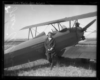 Pilot Jean Allen standing next to bi-plane in Los Angeles, Calif., circa 1930