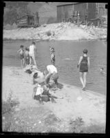 Group of boys in swimsuits or undressing on shoreline of Arroyo Seco creek
