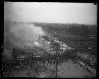 Overhead view of crowds surrounding the Los Angeles Auto Show grounds as smoke rises from the remains of the tents, 1929