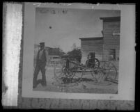 Copy of 1898 photograph of John Leck standing next to his homemade horseless carriage in Calif.