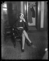 Full length view of actress Lina Basquette sitting in chair smiling, circa 1928