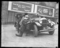 Three Los Angeles plain-clothed police men crouched behind car aiming their guns, circa 1925