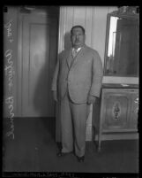 Full length portrait of General Arturo Bernal in suit, standing beside mirror and cabinet, circa 1930