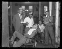 Convicted murderer, Russell Beitzel getting a shave in prison as other inmates look on, Los Angeles, Calif., 1928