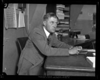 Private Investigator J. Frank Bisbee sitting at a desk in Los Angeles, Calif., circa 1924