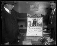 Two Los Angeles policemen displaying the briefcase bomb Timothy P. Blevins used in 1932 attempted bank robbery